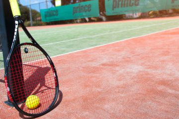 tennis racquet and ball on a court